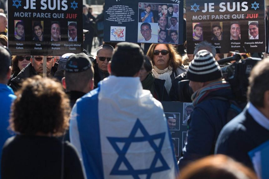 Mourners carry placards bearing portraits of the victims as they gather at a cemetery in Jerusalem on Jan 13, 2015 during the funeral of four Jews killed in an Islamist attack on a kosher supermarket in Paris. The number of anti-Semitic acts doubled