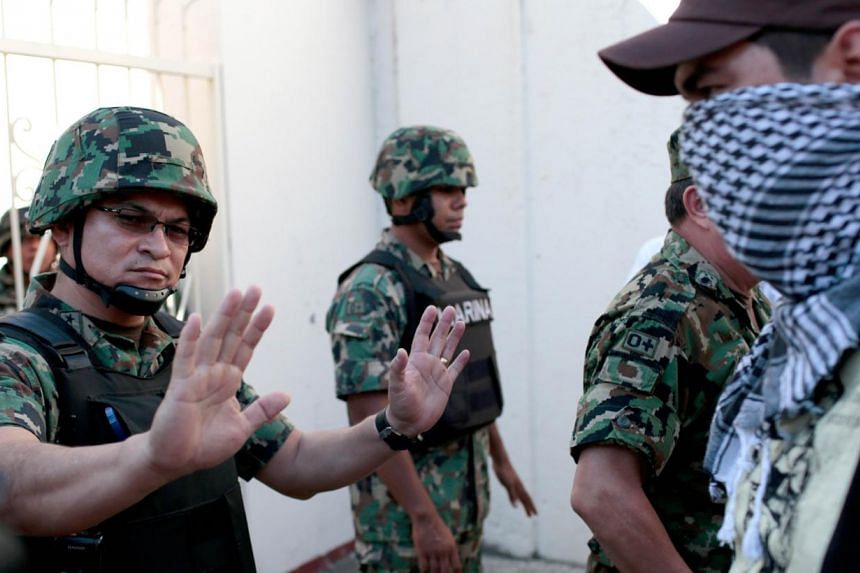 Mexican soldiers block the way to masked people during a protest demanding justice and clarification of the disappearance of 43 students from Ayotzinapa, on Jan 12, 2015, at the naval base in Acapulco, Guerrero State, Mexico. From Tuesday, Jan 27, 20