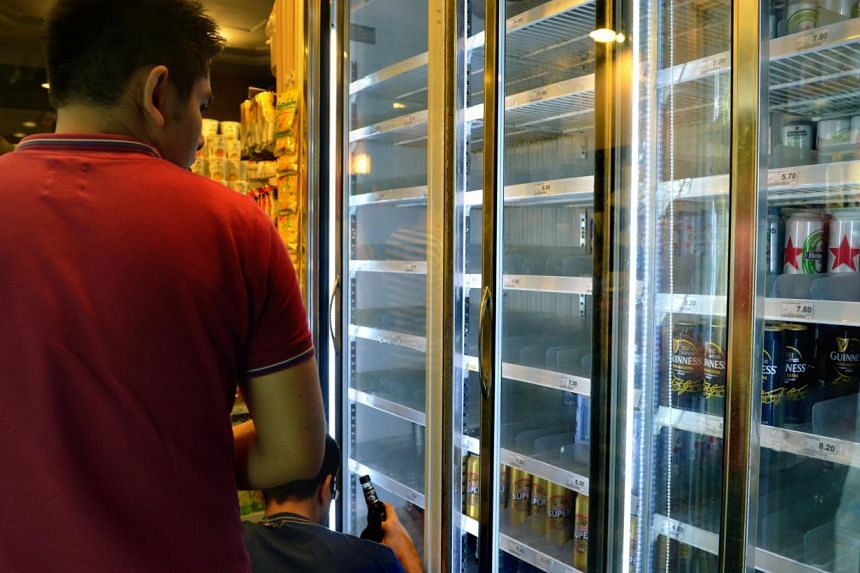 A customer looking at some alcoholic drinks at a 7-Eleven store in Clarke Quay. Four out of five people here support the Bill to outlaw late night drinking, a survey shows. -- ST PHOTO: KUA CHEE SIONG