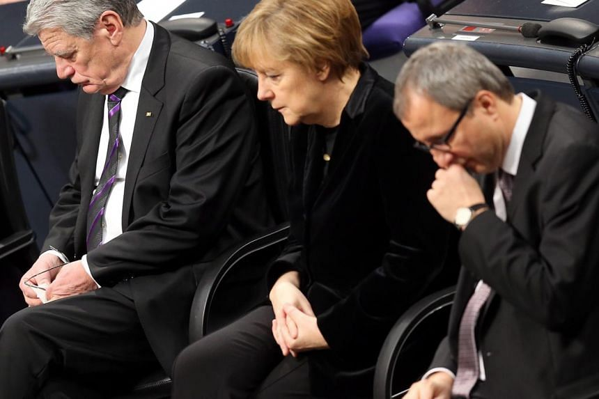 German President Joachim Gauck (left), German Chancellor Angela Merkel (centre) and the President of the Federal Constitutional Court of Germany, Andreas Vosskuhle, attend a commemorative session of the German 'Bundestag' parliament in Berlin on Jan