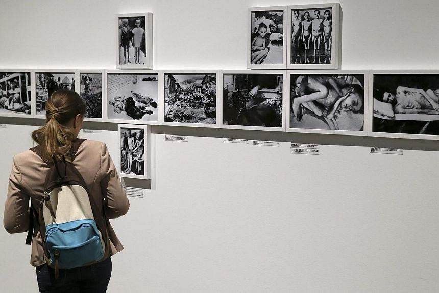 A visitor looks at photos of an exhibition dedicated to the 70th anniversary of liberating the Nazi concentration camp Auschwitz at the Jewish Museum and Tolerance Center in Moscow, Russia on 27 Jan 2015. International Holocaust Remembrance Day this