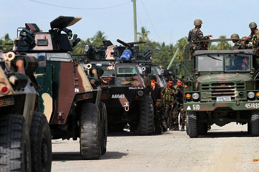 """Philippine military personnel on a lorry going past armoured personnel carriers along the highway in the town of Mamasapano, on Mindanao, on Jan 26, 2015. There is a """"high likelihood"""" that a Malaysian militant suspected of being behind the 2002 Bali"""
