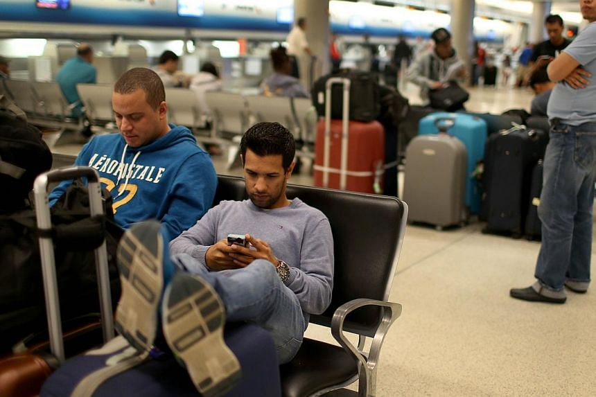 Mr Arthur Hursan (left) and Mr Eduardo Durante sitting together after their flight to New York was cancelled at Miami International Airport in Miami, Florida on Jan 26, 2015. -- PHOTO: AFP