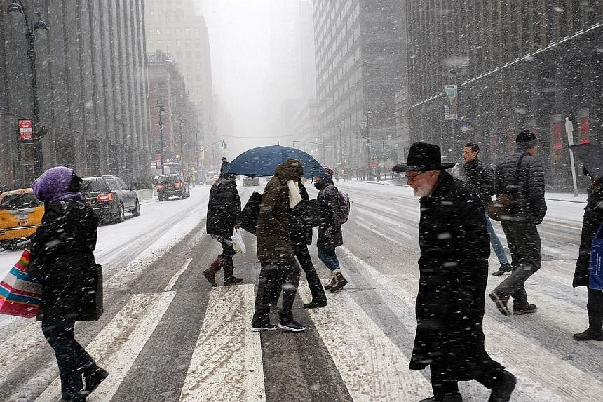 People crossing a city street in a snow storm in New York on Jan 26, 2015. -- PHOTO: AFP