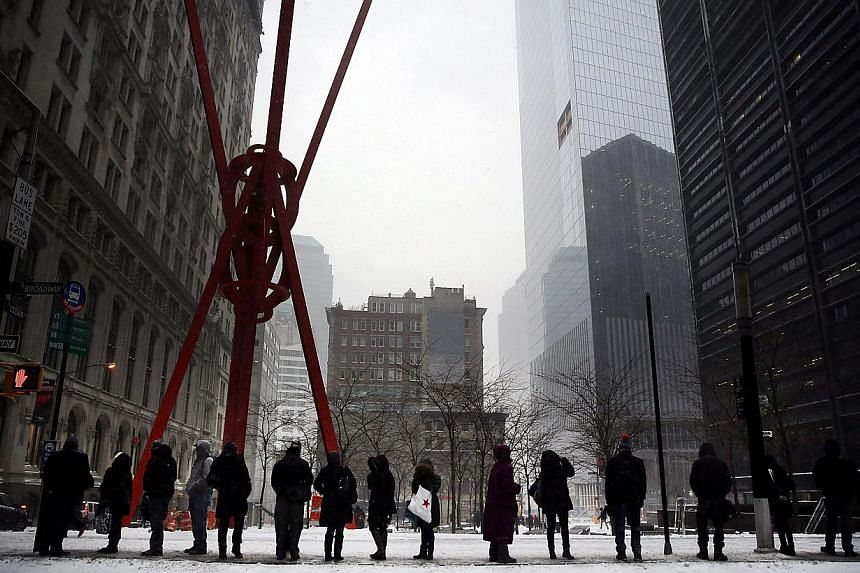 People waiting at a bus stop during heavy snow in the financial district of Manhattan in New York City on Jan 26, 2015. -- PHOTO: AFP