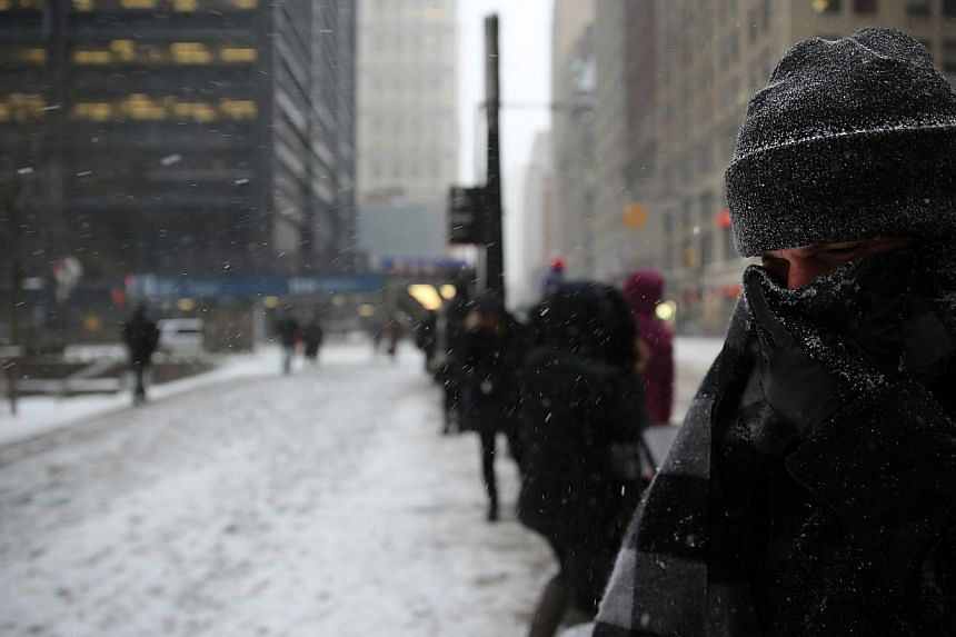 The streets are largely empty as heavy snow began to barrel into the financial district of Manhattan on Monday in New York City. -- PHOTO: AFP