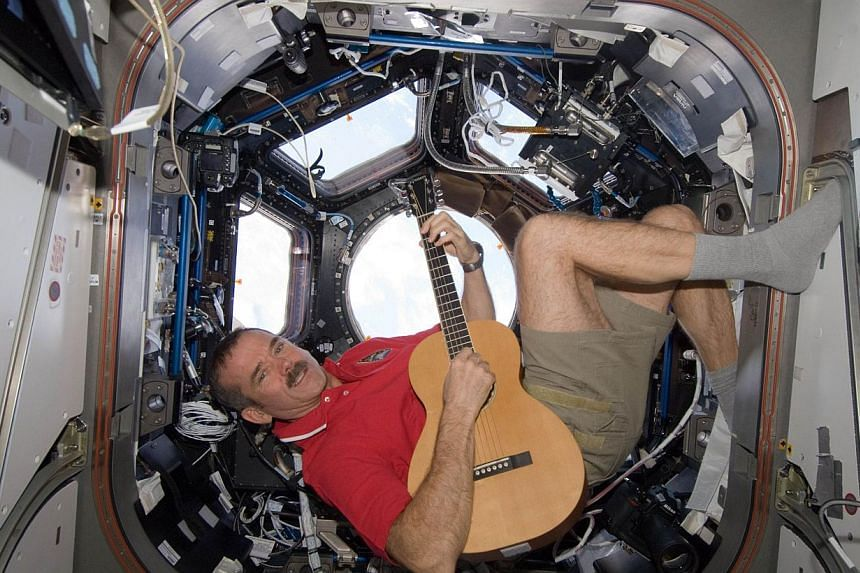 """Canadian Space Agency astronaut Chris Hadfield called the discovery of a moon trailing asteroid 2004 BL86 """"strangely delightful"""" on Twitter. Here in this NASA photo taken on Christmas 2012 he strums his guitar in the International Space Station. Hadf"""