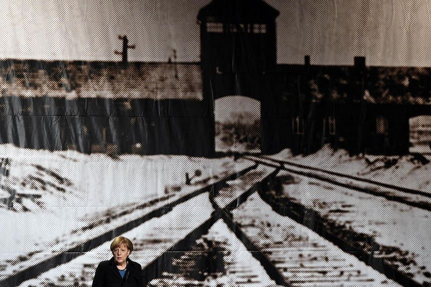 German Chancellor Angela Merkel standing in front of a historic picture of the Auschwitz concentration camp as she gives a speech during the International Auschwitz Committee's remembrance ceremony to mark the 70th anniversary of the liberation of