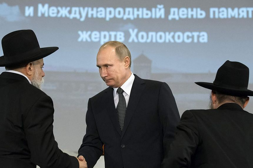 Russian President Vladimir Putin (centre) greets head of the Federation of Jewish Communities of Russia Alexander Boroda (left) and Russian Chief Rabbi Berel Lazar during a ceremony marking the 70th anniversary of the liberation of former Nazi German