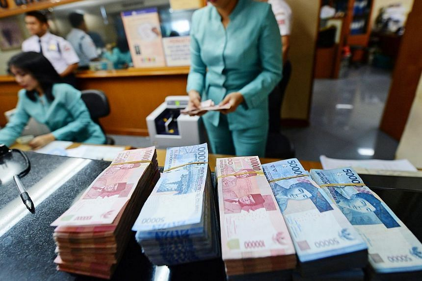 Bundles of Indonesian 100,000 rupiah banknotes and 50,000 rupiah banknotes sit on a counter at a currency exchange office in Jakarta, Indonesia. Indonesia's central bank estimates month-on-month inflation in January tumbled to near zero. -- PHOTO: BL