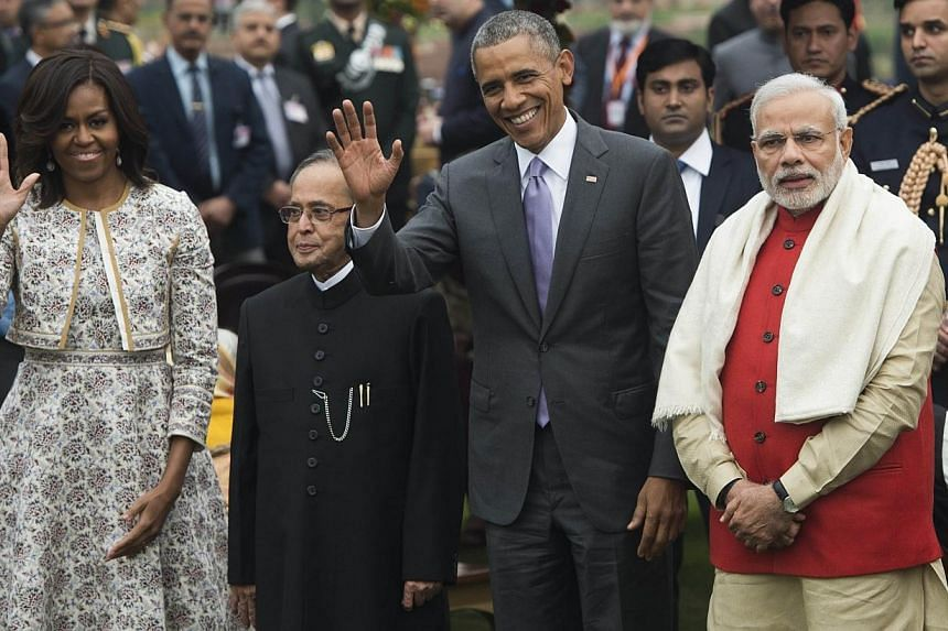 US President Barack Obama (second from right), Indian Prime Minister Narendra Modi (right), Indian President Pranab Mukherjee (second from left) and First Lady Michelle Obama (left) wave during a reception at Rashtrapati Bhawan, the Presidential Pala