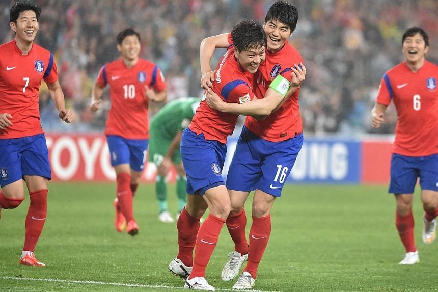 Kim Young Gwon of South Korea (centre left) celebrates scoring their second goal with captain Ki sung Yueng (centre right) against Iraq during the AFC Asian Cup semi-final football match in Sydney on Jan 26, 2015. -- PHOTO: AFP