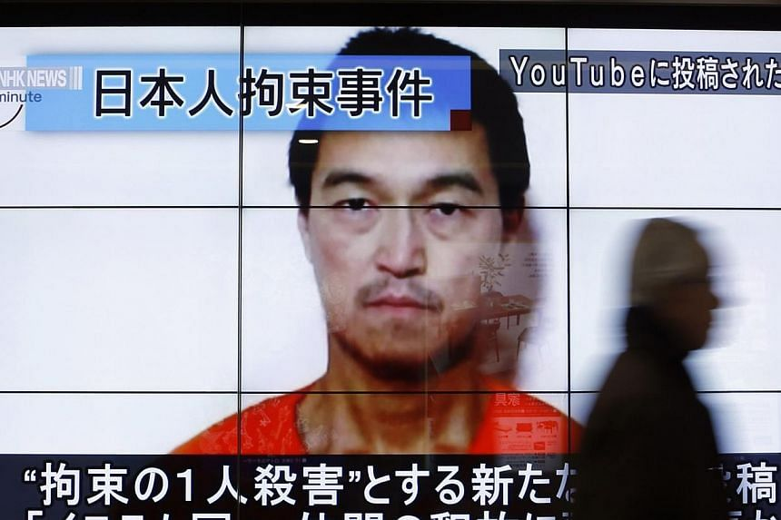 A man walking past screens displaying a news programme showing an image of Japanese journalist Kenji Goto, who is held captive by Islamic State militants, on a street in Tokyo on Jan 25, 2015. -- PHOTO: REUTERS