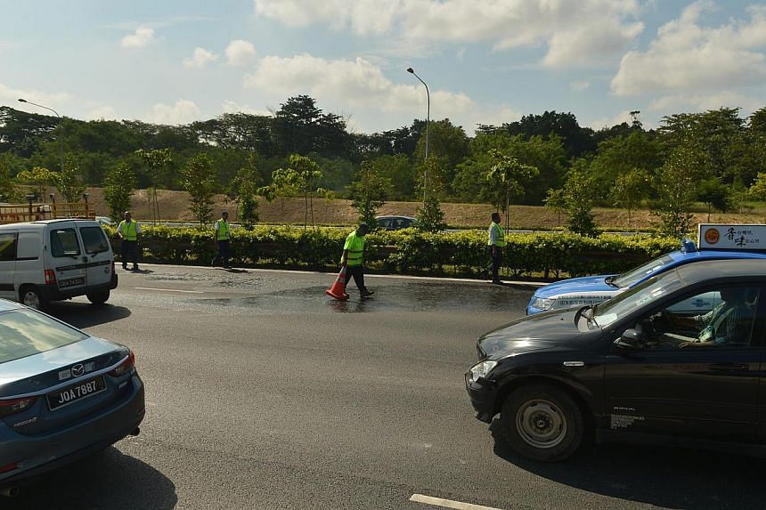 Workers cleaning up the oil leak on the Seletar Expressway. -- ST PHOTO: ALPHONSUS CHERN