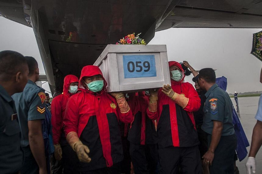 Indonesian rescuers unloading a coffin bearing a body recovered from the underwater wreckage of AirAsia flight QZ8501 from a military plane upon arrival at Surabaya on Jan 23, 2015. -- PHOTO: AFP