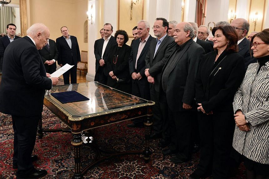 The newly formed government of Prime Minister Alexis Tsipras taking the civil oath in the presence of the Greek President Karolos Papoulias at the presidental palace in Athens on Jan 27, 2015. -- PHOTO: AFP