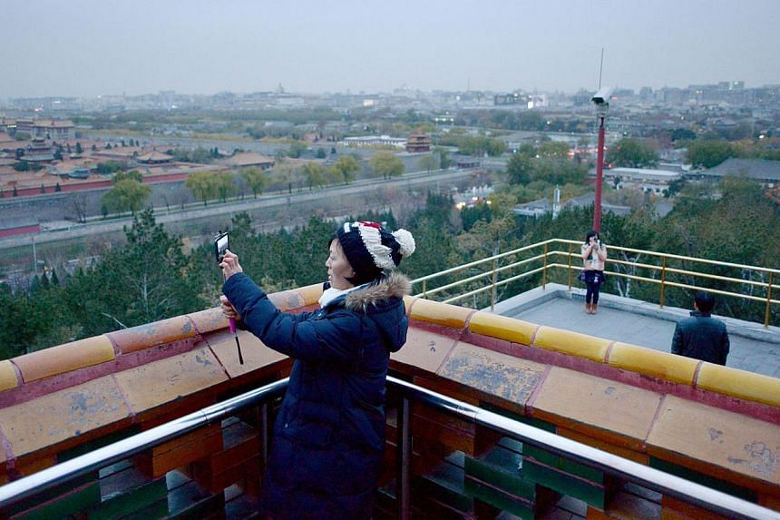 Tourists take a photo near the Forbidden City in Beijing on Nov 27, 2014. The Palace Museum in Beijing, better know as the Forbidden City, unveiled a plan on Tuesday to control the number of visitors after dealing with overwhelming crowds for years.