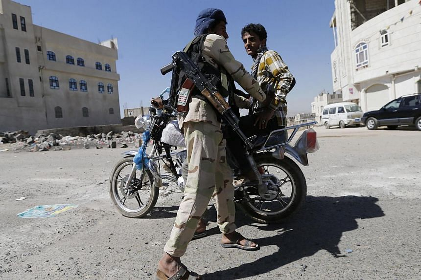 A Huthi fighter in military uniform checks a motorcyclist at a checkpoint in Sanaa Jan 27, 2015. Yemeni Shi'ite militiamen on Tuesday freed a top presidential aide whose kidnapping deepened the country's crippling political crisis, said a person wh