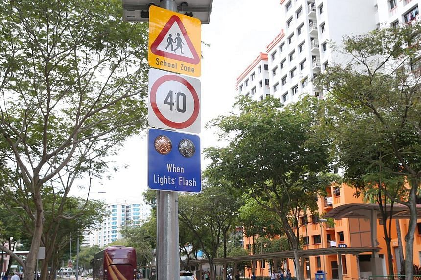 """The sign comprises three smaller signs, a """"children ahead, school zone"""" sign, a """"40kmh"""" speed limit sign, and a """"when lights flash"""" sign with a pair of alternating amber lights. -- ST PHOTO: SEAH KWANG PENG"""