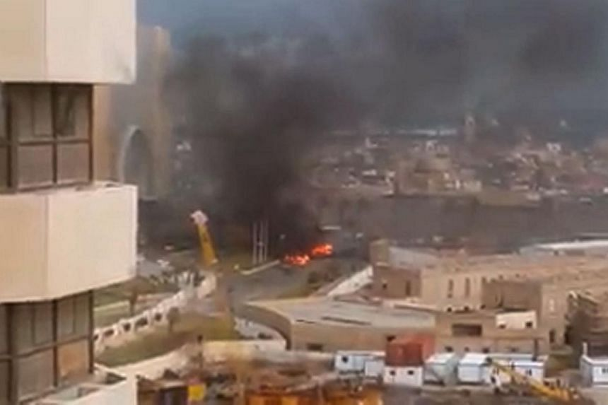 An image grab taken from an AFPTV video shows fire and smoke rising in front of the Corinthia Hotel in Tripoli on Jan 27, 2015 after gunmen stormed the luxury hotel. -- PHOTO: AFP