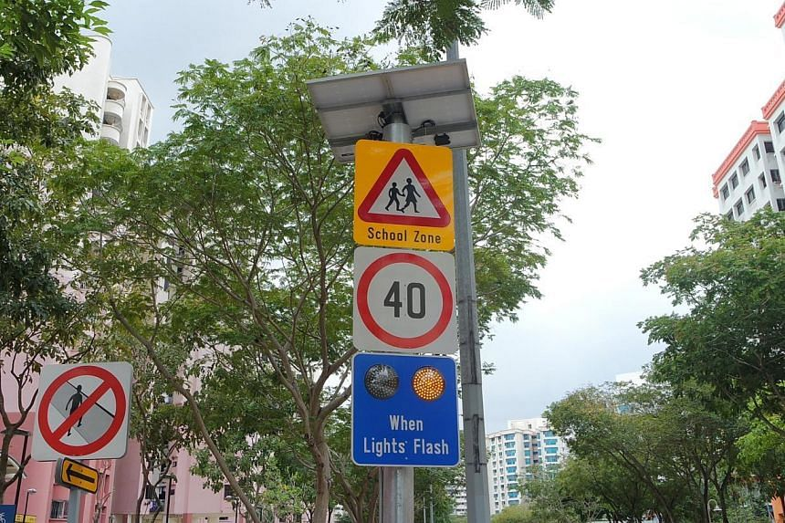 Motorists will be required to reduce their speed limit to 40kmh or under when the amber lights on the sign flash during school peak hours. -- ST PHOTO: MIRANDA YEO