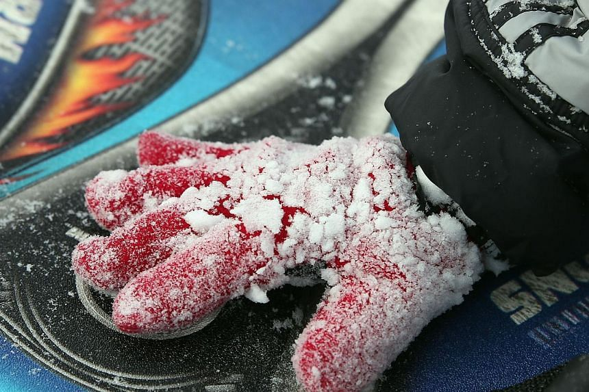 A child's glove is crusted in snow on Tuesday in Old Bethpage, New York from Winter Storm Juno.-- PHOTO: AFP