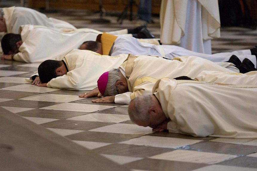 Archbishop of Granada Francisco Javier Martinez and priests prostrate in front of the altar to seek pardon for sexual abuse in the Church at the cathedral in Granada, southern Spain on November 23, 2014. PHOTO: REUTERS