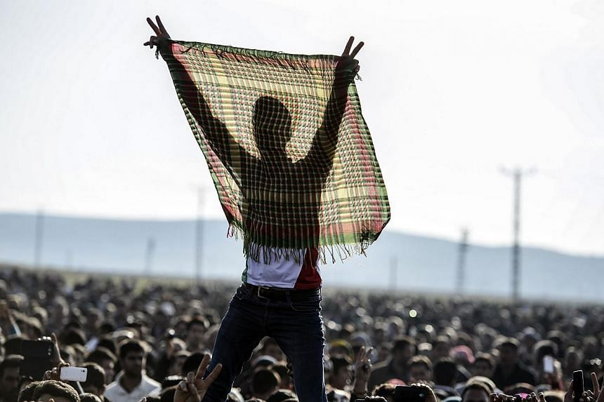 Kurdish people flash the V for victory sign during a celebration rally near the Turkish-Syrian border at Suruc on Tuesday, after ISIS group militants were expelled from the Syrian border town of Kobane, dealing a key symbolic blow to the extremists'