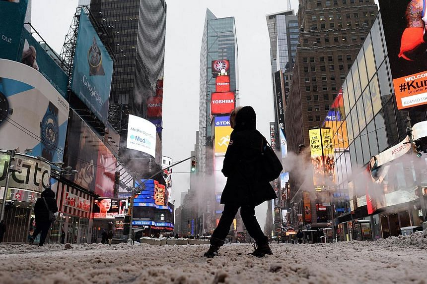A few tourists wandering around nearly deserted New York's Times Square in what is normally a crowed morning rush hour after a snowstorm on Tuesday. A blizzard initially billed as possibly one of the worst ever in New York left only moderate snow in