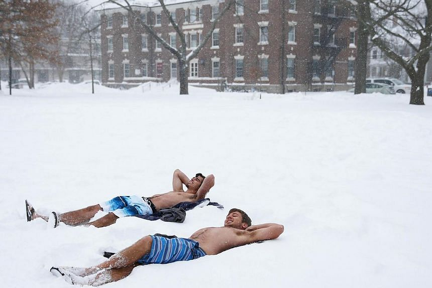 Students lying down in their bathing suits on the Quad, on the campus of Harvard University on Tuesday in Cambridge, Massachusetts. -- PHOTO: AFP