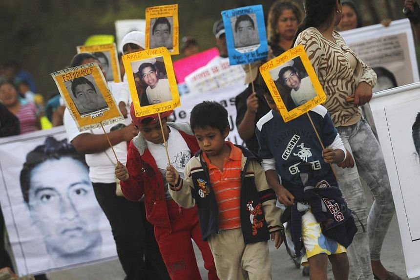 People carrying pictures of some of the 43 students who went missing in September in Mexico during a demonstration in Tixtla, on the outskirts of Chilpancingo, in the Mexican state of Guerrero, on Dec 7, 2014. -- PHOTO: REUTERS