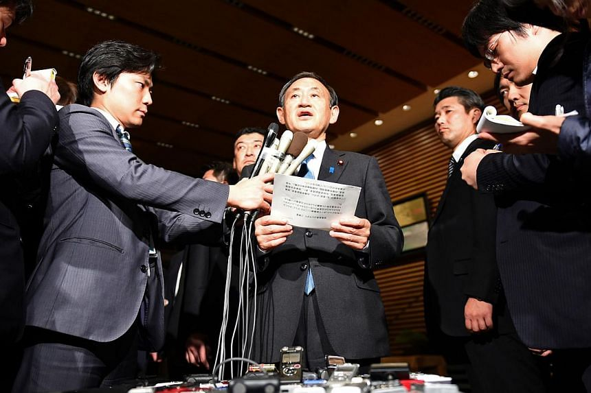 Japanese Chief Cabinet Secretary Yoshihide Suga (centre) speaks to reporters at the prime minister's official residence in Tokyo early on Jan 28, 2015.Japan has asked Jordan for help after the Islamic State in Iraq and Syria militant group thre