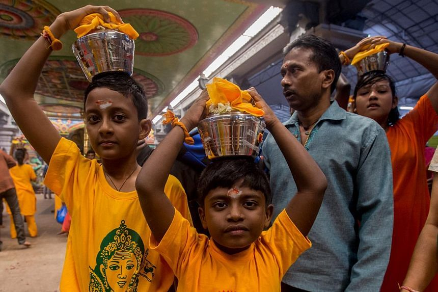 Children carrying palkudam during last year's Thaipusam procession. The annual Thaipusam Festival procession will begin at 12.05am on Feb 3 this year, the Hindu Endowments Board announced on Wednesday. -- PHOTO: TAMIL MURASU FILE