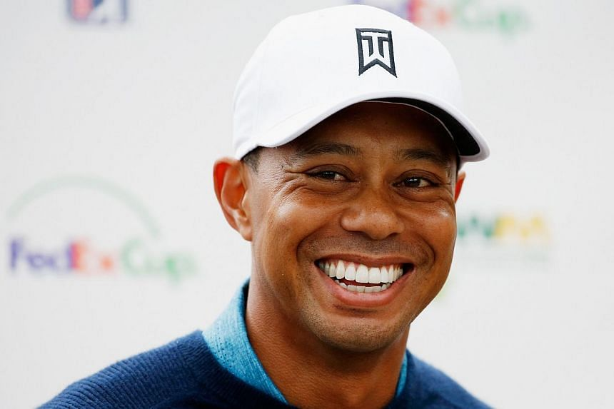 Tiger Woods, who had a front tooth knocked out by a video cameraman last week, displayed a full smile Tuesday (above) after a nine-hole practice round ahead of the Phoenix Open. -- PHOTO: AFP