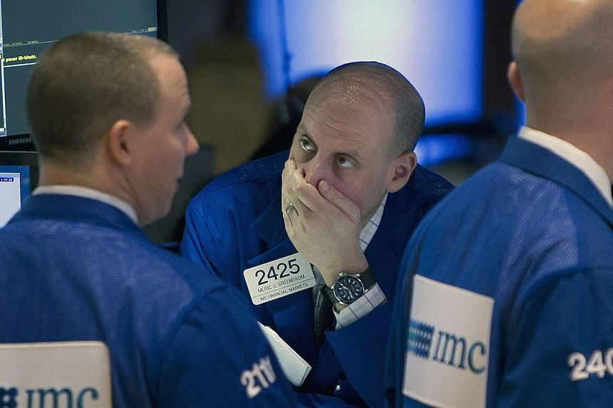 Traders work on the floor of the New York Stock Exchange on Jan 27, 2015. Wall Street stocks finished sharply lower Tuesday following a disappointing stream of corporate earnings and mixed US economic data.-- PHOTO: REUTERS