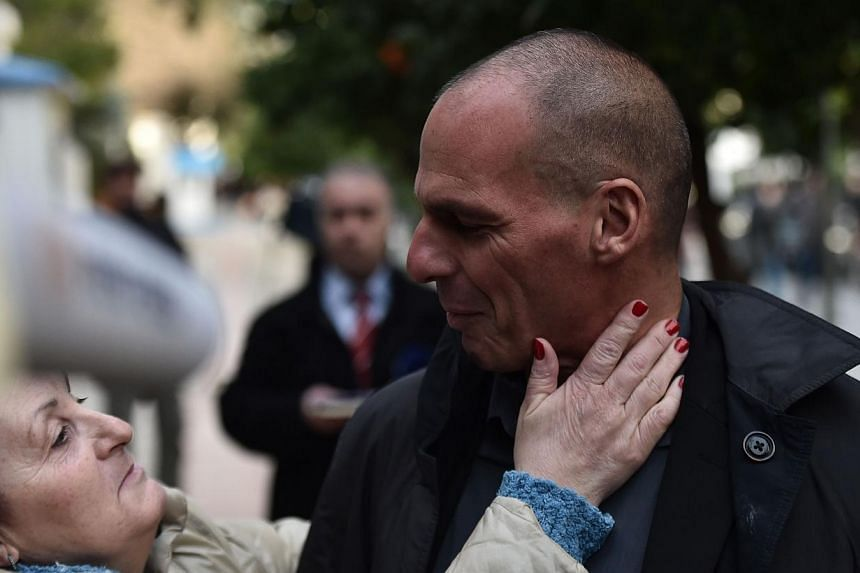 Greece's newly appointed finance minister Yanis Varoufakis (right) is greeted as he walks along a street in Athens on Jan 27, 2015. The53-year-old economisthas written several books andworked as a consultant for computer game compan