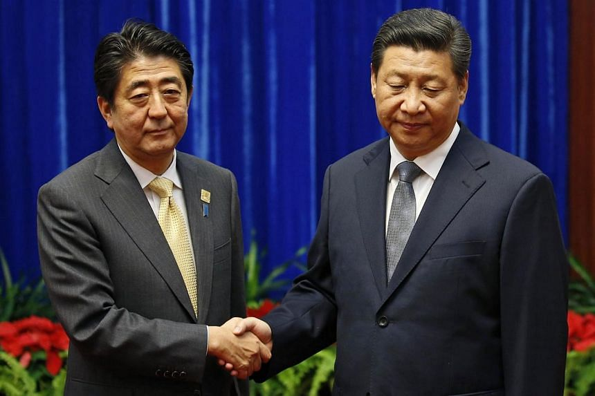 China's President Xi Jinping (right) shakes hands with Japan's Prime Minister Shinzo Abe during their meeting at the Great Hall of the People, on the sidelines of the Asia Pacific Economic Cooperation (APEC) meetings, in Beijing in this Nov 10, 2014