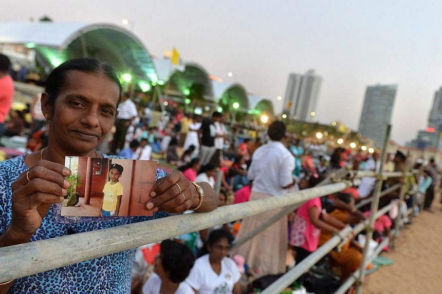 A Sri Lankan Catholic devotee holds a photograph of his close family members on his arrival the day before the celebration of the Papal Mass by Pope Francis in the capital Colombo on Jan 13, 2015. -- PHOTO: AFP