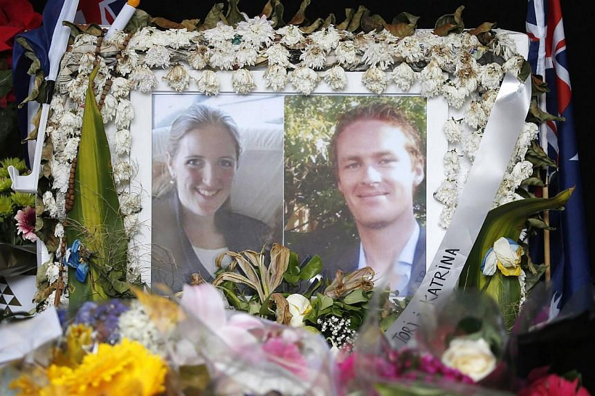 Photographs of Sydney's cafe siege victims, lawyer Katrina Dawson (left) and cafe manager Tori Johnson displayed  in a floral tribute near the site of the siege. Ms Dawson was killed by ricochets of a police bullet or bullets, an inquest heard o