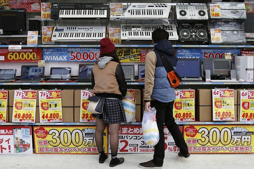 People trying out laptops displayed at an electronics retail store in Tokyo on Nov 16, 2014. Japanese retail sales unexpectedly fell in December, underscoring challenges to Prime Minister Shinzo Abe's effort to stoke a recovery in the world's third-b