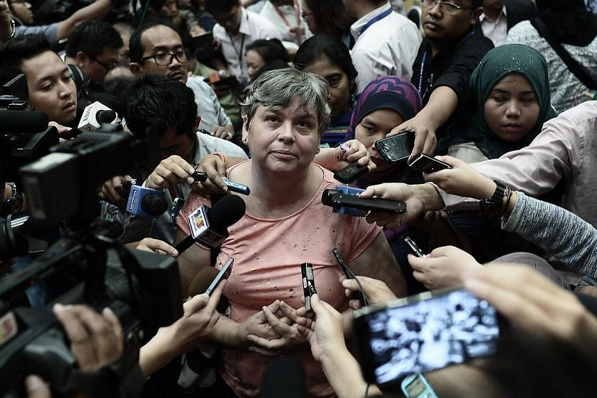 A relative (centre) of a passenger of the missing Malaysia Airlines flight MH370 talking to journalists at a press conference in Putrajaya on Jan 29, 2015. -- PHOTO: AFP