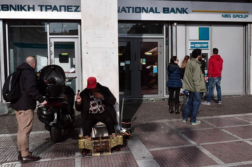 People waiting in front of a branch of the National Bank in central Athens on Jan 21, 2015. Greek banks raised more than US$11.5 billion (S$15.6 billion)in additional share sales in 2014, but lost about US$11.4 billion in market value thi