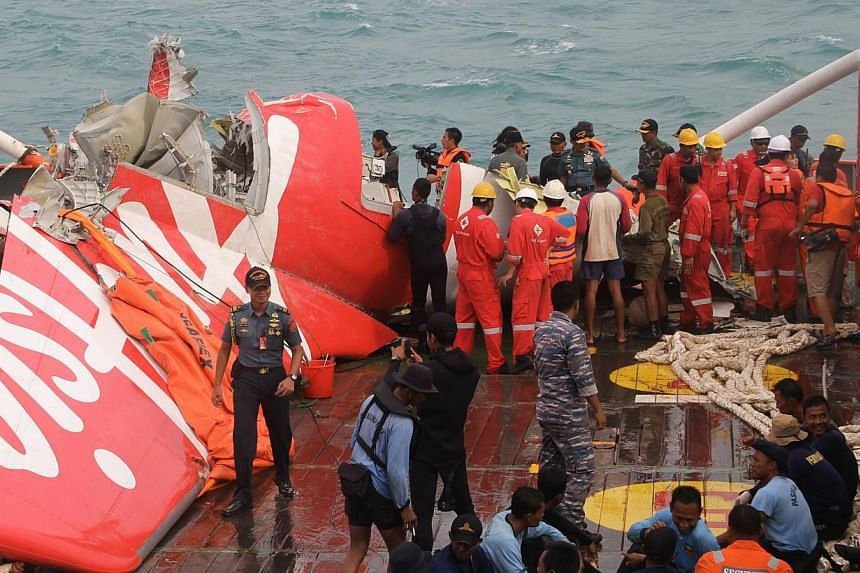 The wreckage of AirAsia flight QZ8501 is lifted into a ship at sea south of Borneo island on Jan 10, 2015. -- PHOTO: AFP