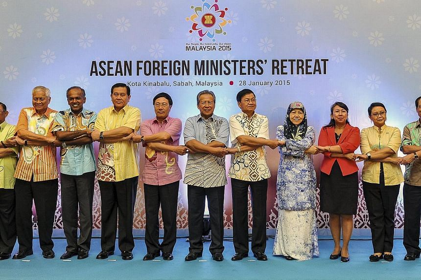 Asean's Foreign Ministers and delegates cross arms and hold hands during the Asean Foreign Ministers Retreat in Kota Kinabalu, Malaysia, on Jan 28, 2015. -- PHOTO: EPA