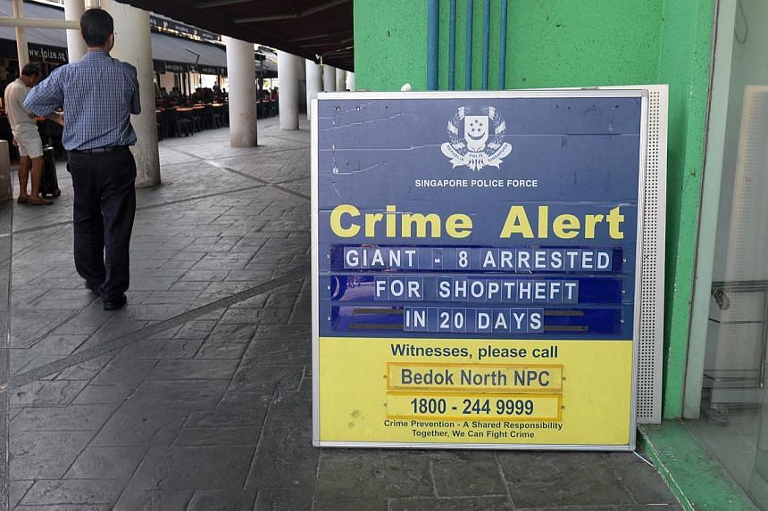 A crime alert sign put up by Neighbourhood Police Post (NPCCs) just outside Giant supermarket at Bedok Market Place on May 13, 2014. -- ST PHOTO: AZIZ HUSSIN