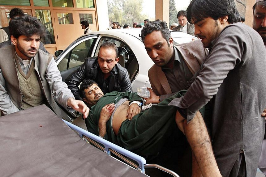 Afghan men carry a wounded man at a hospital in Jalalabad, after a suicide attack which targeted funeral prayers in Laghman province, Jan 29, 2015. -- PHOTO: REUTERS