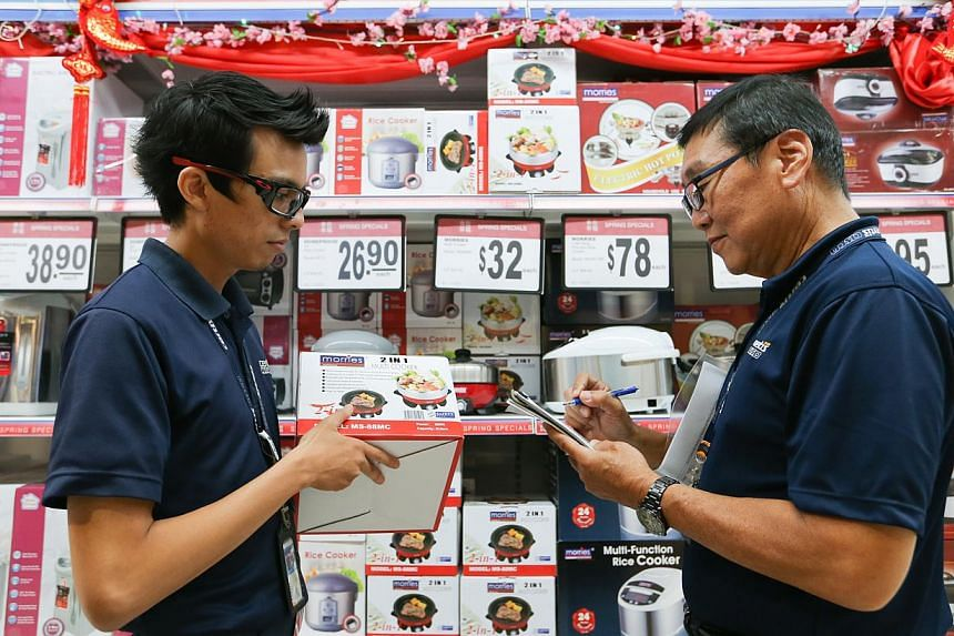 Certis Cisco enforcement officers, Mr Safiuddin Bin Roshan (left) and Mr Wee Peng Soon checking for the Safety Mark sticker on electronic products sold in NTUC. -- ST PHOTO: ONG WEE JIN