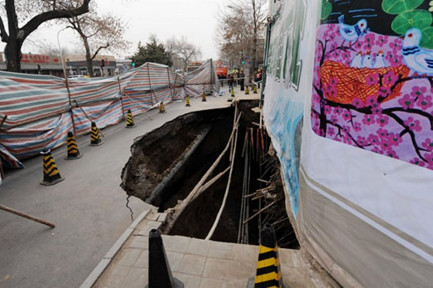 This photo taken on the morning of Saturday, Jan 24, 2015, shows a big hole on a street in Beijing's Xicheng district. The hole has since been filled in with 1,400 cu m of concrete. -- PHOTO: CHINA DAILY/ASIA NEWS NETWORK