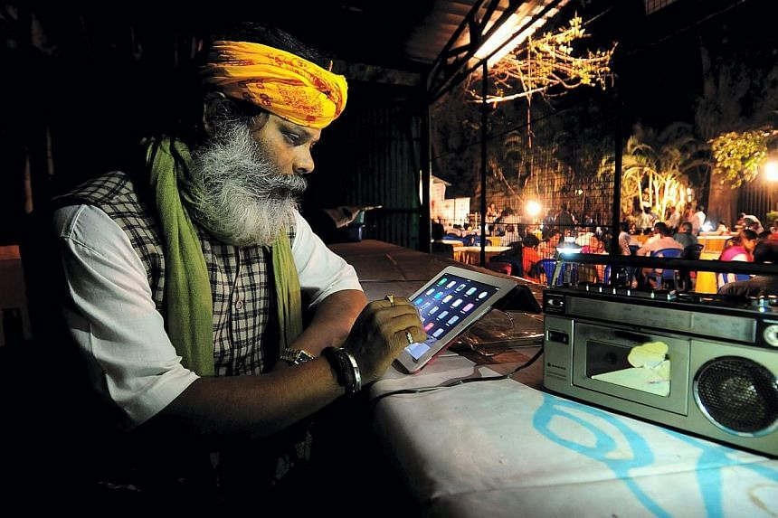 """An Indian man listens to Prime Minister Modi's special address via All India Radio in Bangalore, India, on Jan 27, 2015. In a bid to boost domestic manufacturing through its """"Make in India"""" programme, the Narendra Modi government may have taken an in"""