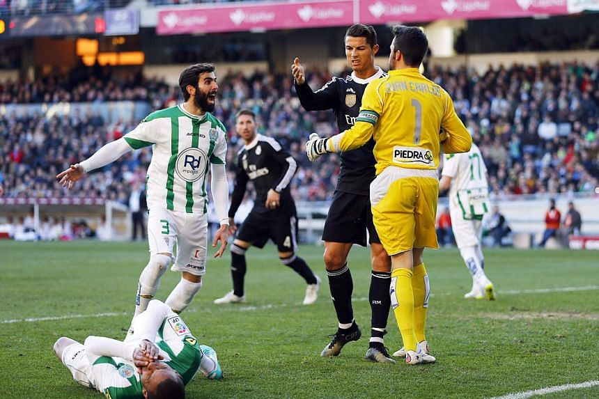 Real Madrid's Cristiano Ronaldo (second right) reacts as Cordoba's Edimar Fraga (bottom) lies on the pitch during their Spanish First Division soccer match at El Arcangel stadium in Cordoba, Jan 24, 2015. -- PHOTO: REUTERS